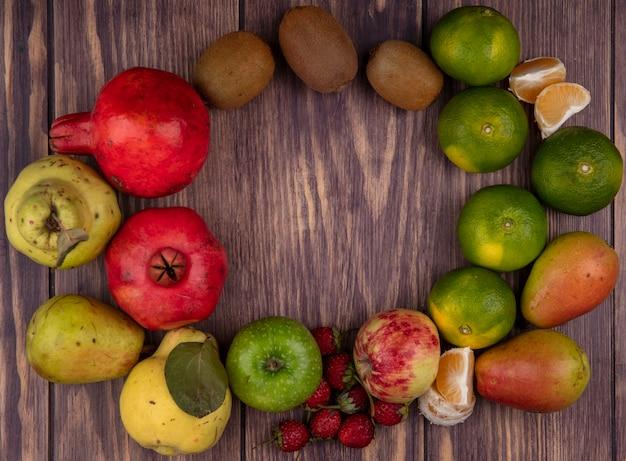 Vista superior cópia espaço maçãs coloridas com kiwi, tangerinas, peras, morangos e romãs na parede de madeira