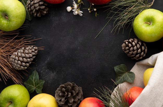 Vista superior cópia espaço maçãs coloridas e cones de abeto nas bordas em um fundo preto