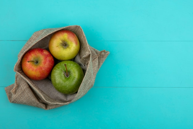 Vista superior cópia espaço maçãs coloridas em um saco de estopa sobre um fundo azul claro