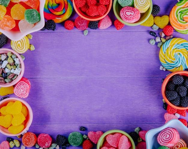 Vista superior cópia espaço marmelada multicolorida com pedras de chocolate e pingentes coloridos em pires para geléia em um fundo roxo