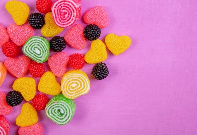 Vista superior cópia espaço marmelada multicolorida em formas diferentes, sobre um fundo rosa claro