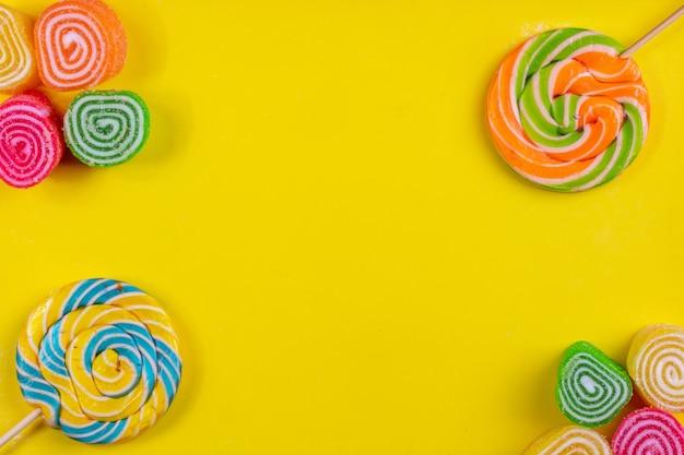 Vista superior cópia espaço marmeladas multi-coloridas com pingentes multi-coloridas sobre um fundo amarelo
