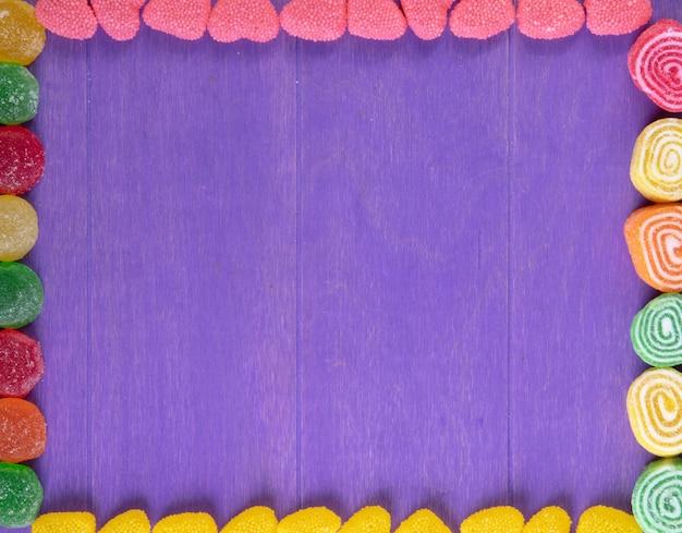 Vista superior cópia espaço marmeladas multi-coloridas sobre um fundo roxo