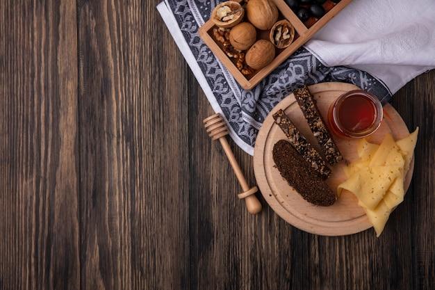 Vista superior cópia espaço mel em uma jarra com pão preto e queijo em um carrinho com nozes em um fundo de madeira
