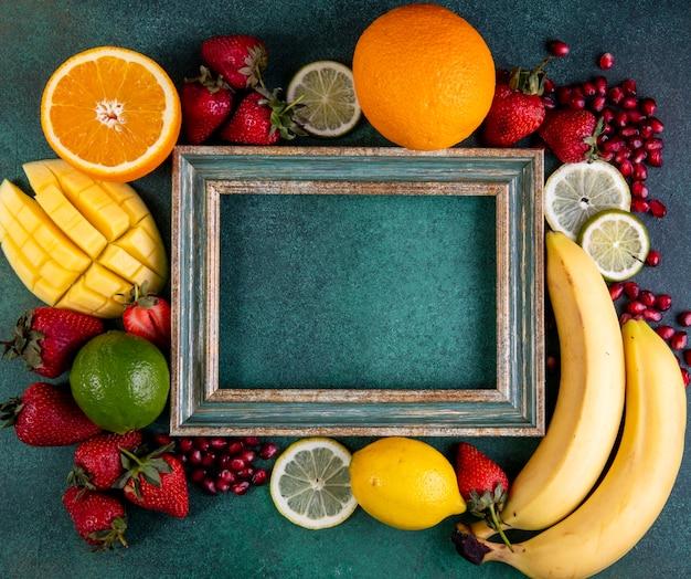 Vista superior cópia espaço mix de frutas manga banana morangos limão laranja com moldura em verde
