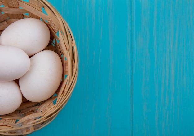 Vista superior cópia espaço ovos de galinha na cesta em fundo turquesa