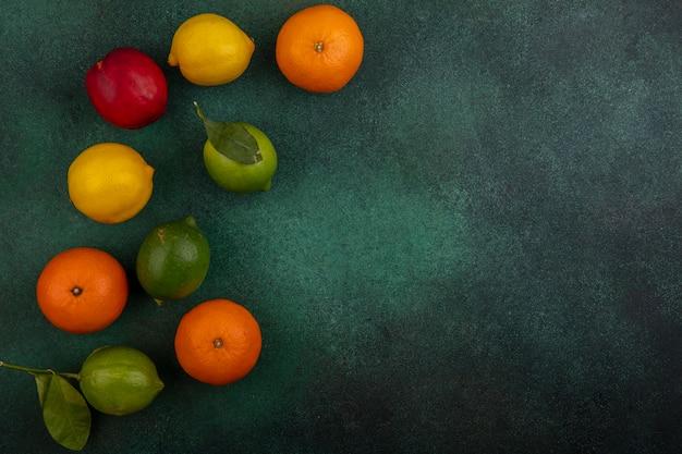 Vista superior cópia espaço pêssego com limão, lima e laranjas em um fundo verde