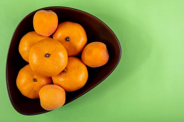 Vista superior cópia espaço tangerinas em uma tigela na luz verde