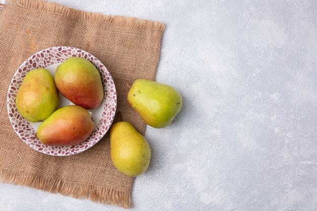 Vista superior copie as peras em um prato em um guardanapo bege em um fundo branco
