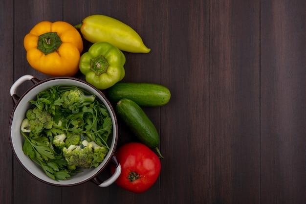 Vista superior copie brócolis em uma panela com salsa, pepino e pimentão em fundo de madeira