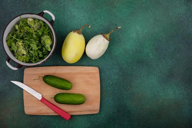 Vista superior copie espaços verdes em uma panela com pepinos em uma tábua de cortar com uma faca e berinjelas brancas em um fundo verde
