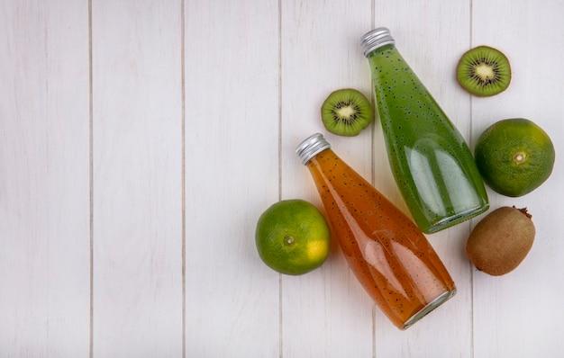 Vista superior copie garrafas de suco com tangerinas e kiwi na parede branca