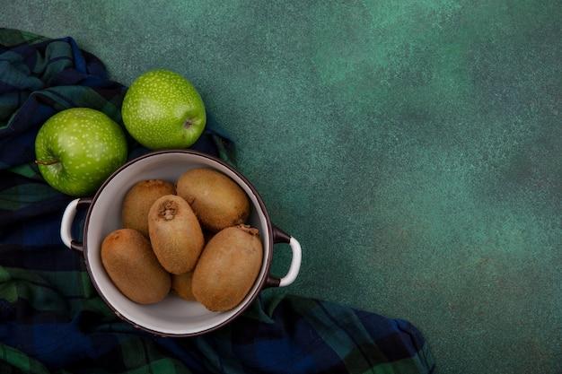 Vista superior copie kiwi espacial em uma panela com maçãs verdes em uma toalha xadrez em um fundo verde