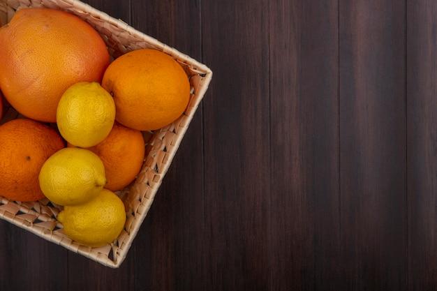 Vista superior copie laranjas em uma cesta com limões e toranjas em um fundo de madeira
