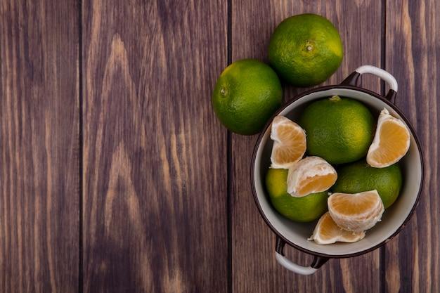 Vista superior copie tangerinas em uma panela na parede de madeira