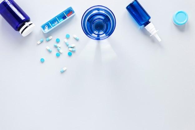 Vista superior copo de água com analgésicos em cima da mesa