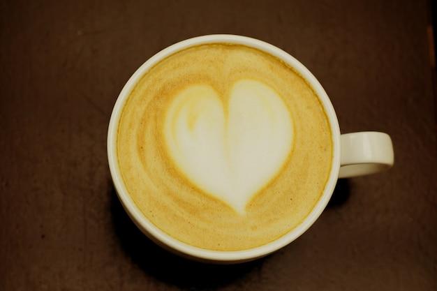 Vista superior copo grande de cappuccino acabado de fazer com espuma macia e coração na mesa de madeira.