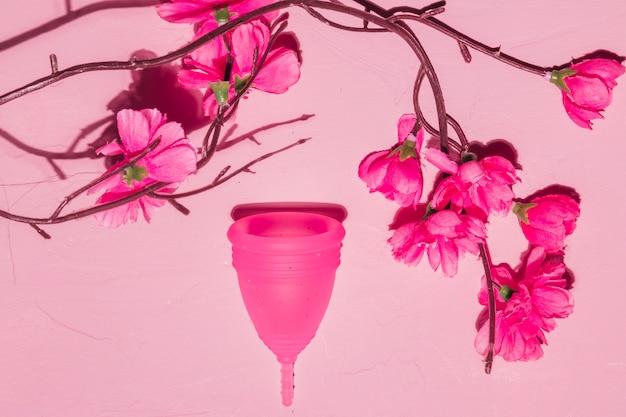 Vista superior copo menstrual com ramo de flores