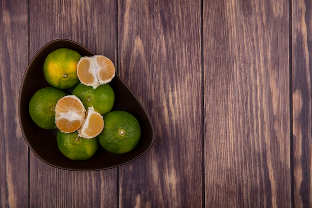 Vista superior copy space tangerinas em tigela com fatias descascadas na parede de madeira