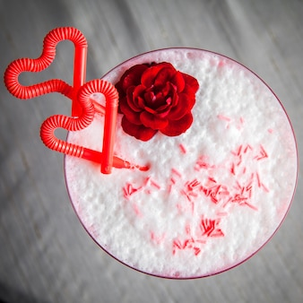Vista superior coquetel de morango com suco de palha em forma de coração e flores em vidro redondo