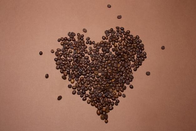 Vista superior coração feita de grãos de café sobre um fundo marrom