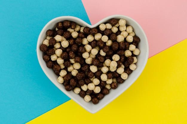 Vista superior coração forma tigela cheia com cereais