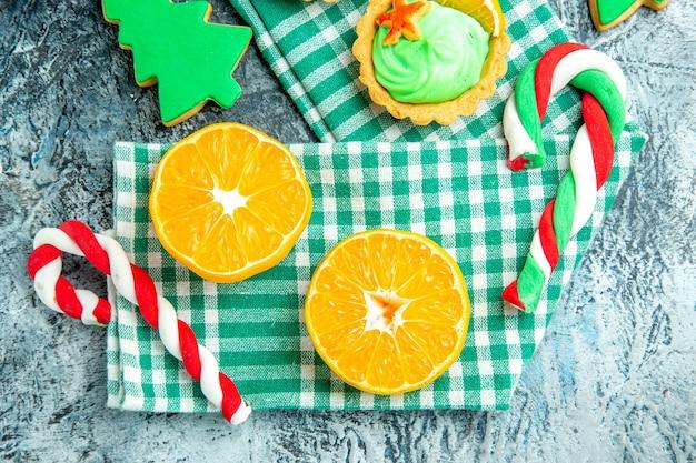 Vista superior, corte de laranjas, doces de árvore de natal em toalha de cozinha quadriculada branca verde na mesa cinza