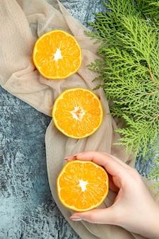 Vista superior, corte de laranjas em pinhas femininas em um xale bege na superfície escura