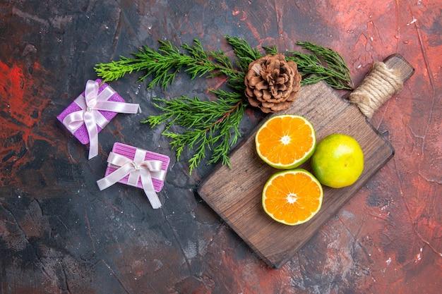Vista superior, corte de laranjas na tábua de cortar galho de árvore de pinho com presentes de natal de cone na superfície vermelha escura