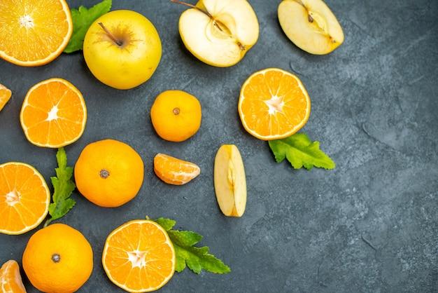 Vista superior, corte de maçãs e laranjas em fundo escuro