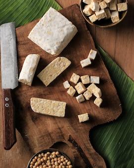 Vista superior, corte e corte de tempeh cru em uma tábua de madeira acima da mesa marrom rústica