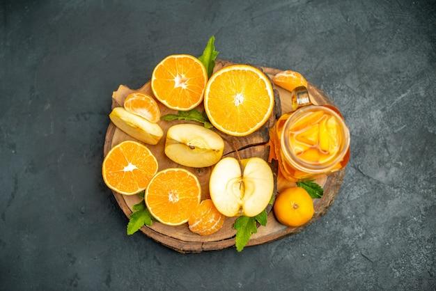 Vista superior corte laranjas e maçãs cortadas laranja na superfície escura