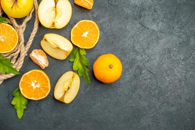 Vista superior corte laranjas e maçãs em superfície escura