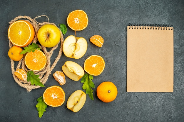 Vista superior corte laranjas e maçãs em um bloco de notas na superfície escura