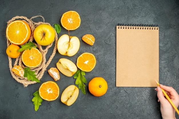 Vista superior, corte laranjas e maçãs, um lápis bloco de notas em uma mão feminina na superfície escura