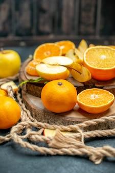 Vista superior corte maçãs e laranjas na placa de madeira coquetel em fundo escuro