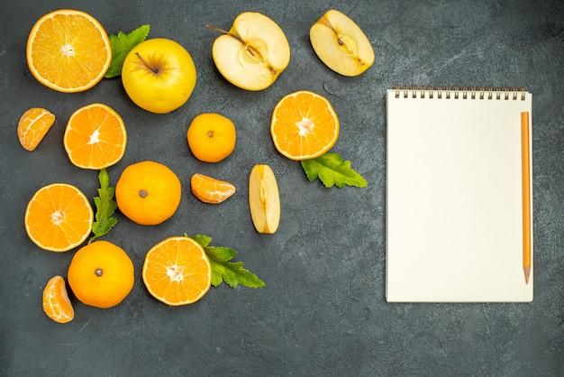 Vista superior corte maçãs e laranjas um caderno em fundo escuro