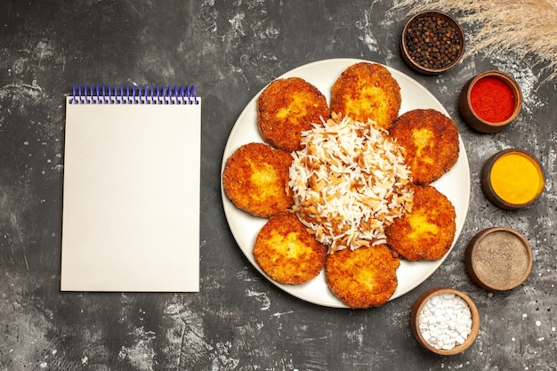 Vista superior costeletas fritas com arroz cozido e temperos na mesa escura de pratos de comida foto de carne