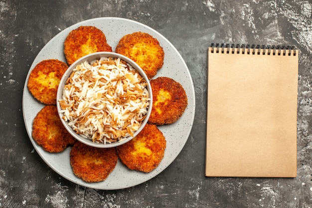 Vista superior costeletas fritas com arroz cozido em rissole de comida de superfície escura