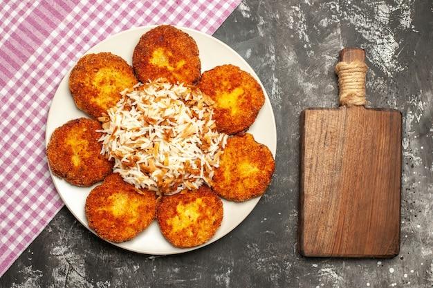 Vista superior costeletas fritas com arroz cozido em um rissole de prato de carne de superfície escura