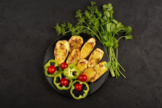 Vista superior cozida berinjela dentro de chapa preta, juntamente com pimentão verde fatiado e tomate cereja vermelho no escuro