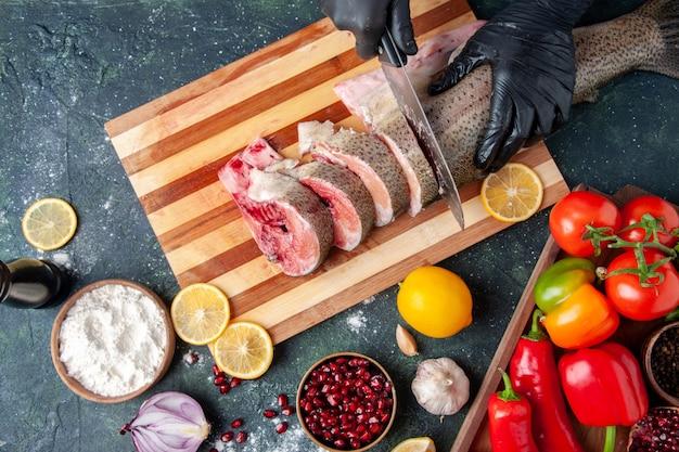 Vista superior cozinheiro cortando peixe cru na tábua de legumes na tábua de madeira limão na mesa