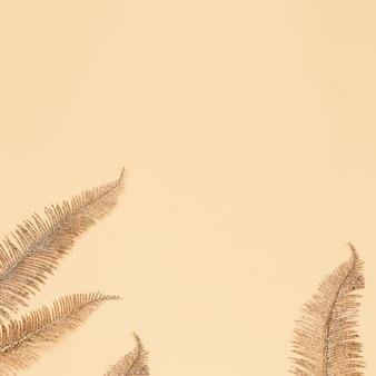Vista superior criativa com folhas de palmeira coloridas douradas sobre fundo de papel. conceito mínimo de verão.