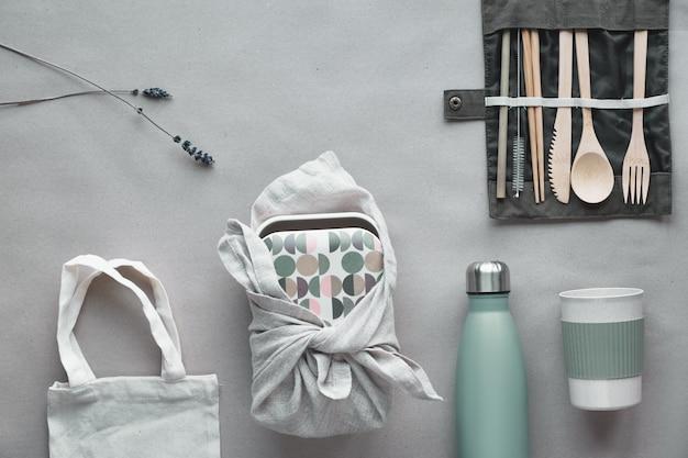 Vista superior criativa, kit de almoço embalado com zero desperdício, lancheira para viagem definida no saco de algodão, organizador de talheres de bambu, caixa reutilizável e xícara de café de bambu.