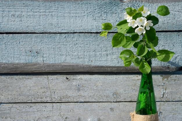 Vista superior criativa macieira florescendo brunch de flores em frasco de vidro verde sobre fundo de madeira rústico