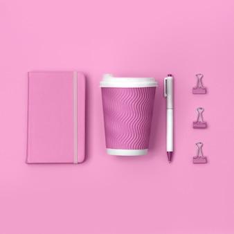 Vista superior criativa plana leigos de mesa de mulher com papelaria rosa.