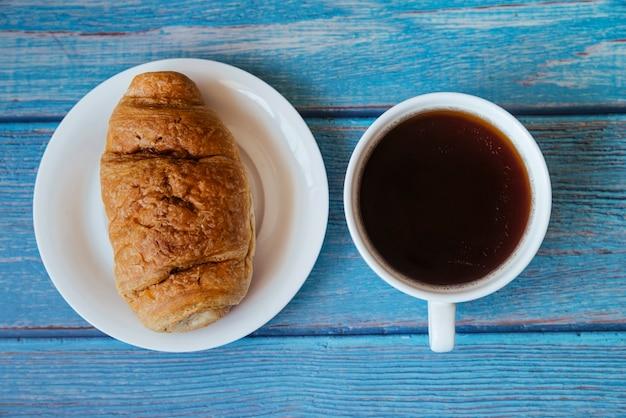 Vista superior croissant e café na mesa de madeira