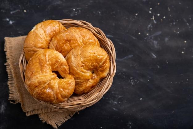 Vista superior croissant em uma cesta de vime colocada sobre um piso preto