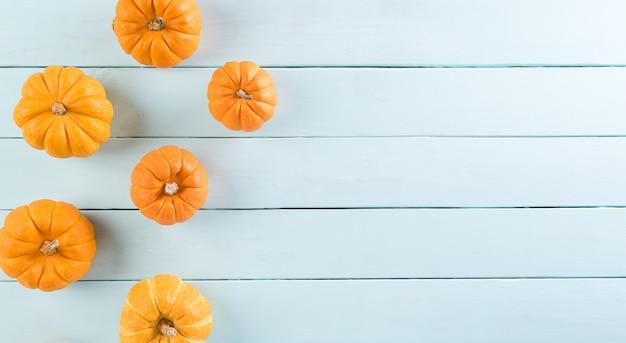 Vista superior da abóbora laranja em fundo de madeira pastel, com espaço de cópia para o texto. halloween, conceito de decoração de outono.