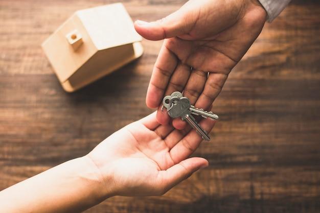 Vista superior da agência de banqueiro dar chave de casa para o comprador